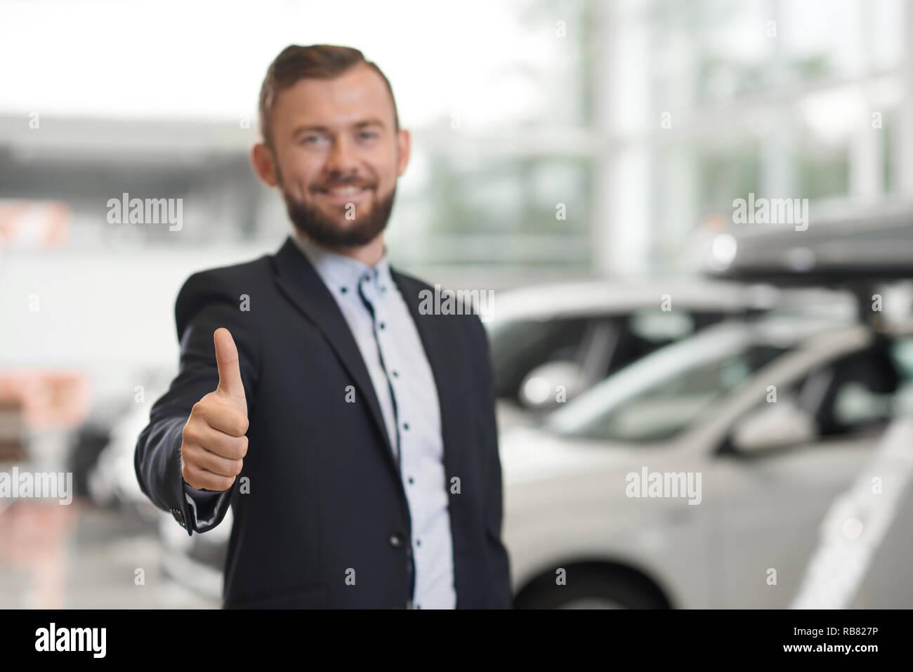 Cliente satisfecho del concesionario de coches mostrando el pulgar hacia arriba. Apuesto hombre barbado mirando a la cámara, sonriendo, posando. Empresario vistiendo la camiseta oficial y chaqueta azul oscuro. Imagen De Stock