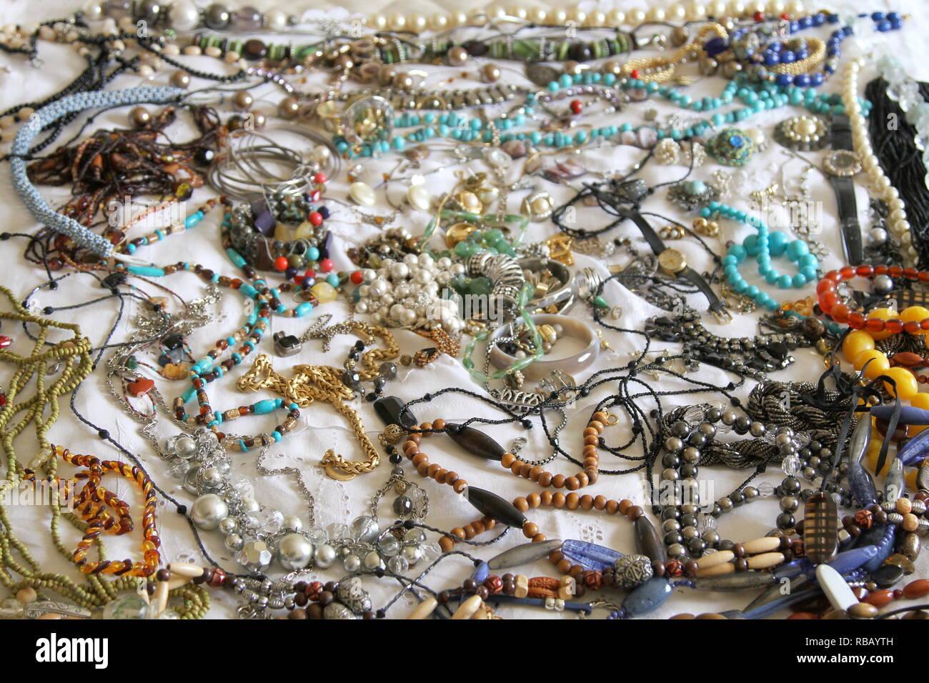 Joyería. Una colección de joyas, sentado sobre una cama con una sábana blanca. Joyas. Los objetos de valor. La propiedad personal. Valor sentimental. Las piedras. Las perlas. Cordones. Collares. Pulseras. Un reloj de muñeca. Multicolor. Surtido. Foto de stock