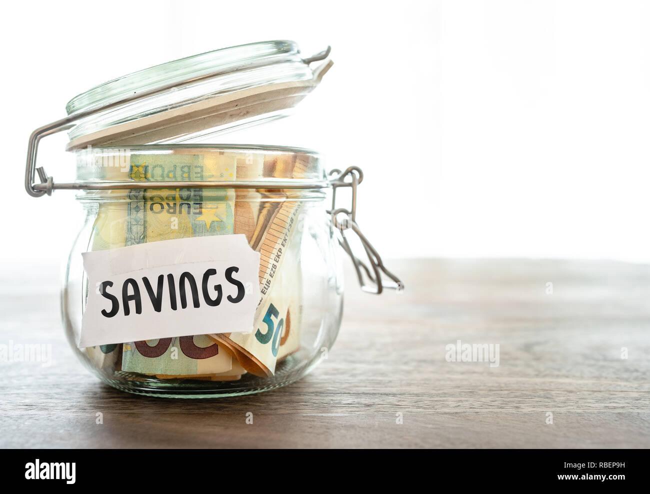 El papel moneda en la jarra sobre la mesa de madera Foto de stock