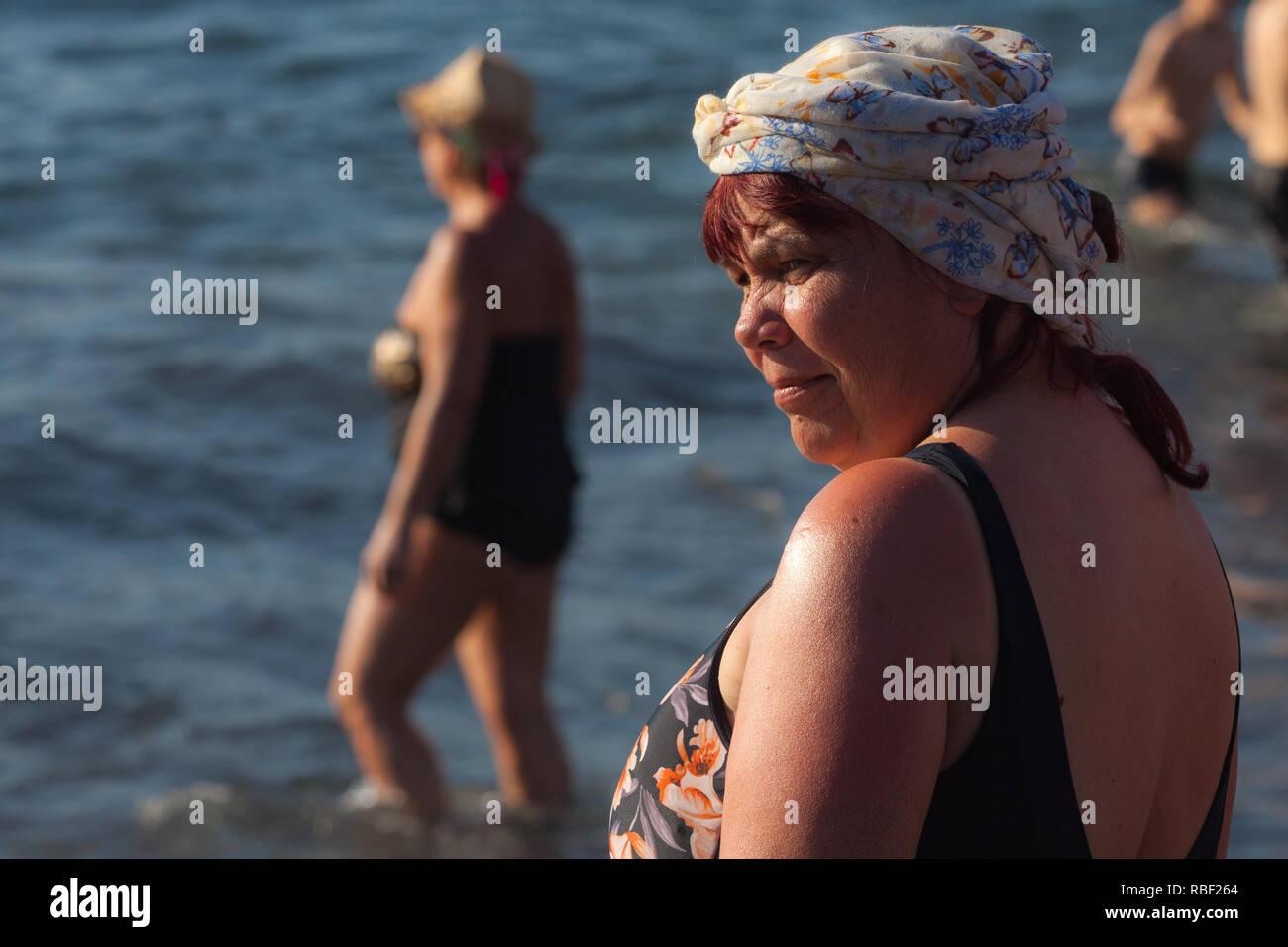 Una bonita foto de una mujer encantadora disfrutando de una soleada playa Imagen De Stock