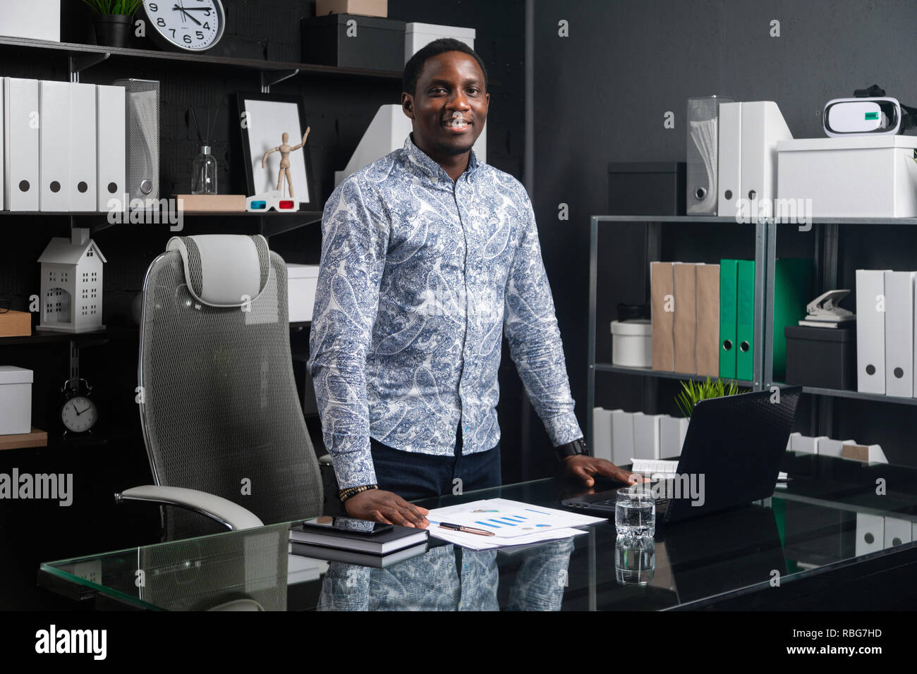 Retrato de tres cuartas partes de largo negro joven empresario parado cerca del escritorio de oficina Imagen De Stock
