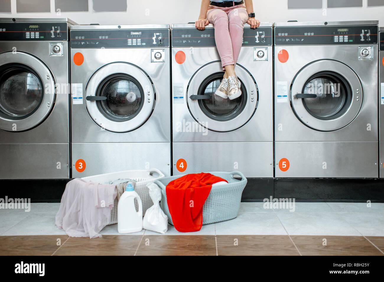 2f9835b4c058f Mujer sentada en la lavadora esperando el lavado en la lavandería de  autoservicio con cestas llenas de ropa. Imagen recortada con ninguna cara