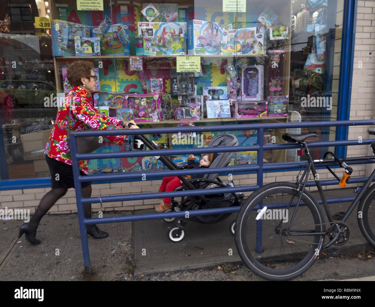 La abuela de llevar a su nieto a una tienda de juguetes, en la sección de Park Slope de Brooklyn, NY. Imagen De Stock