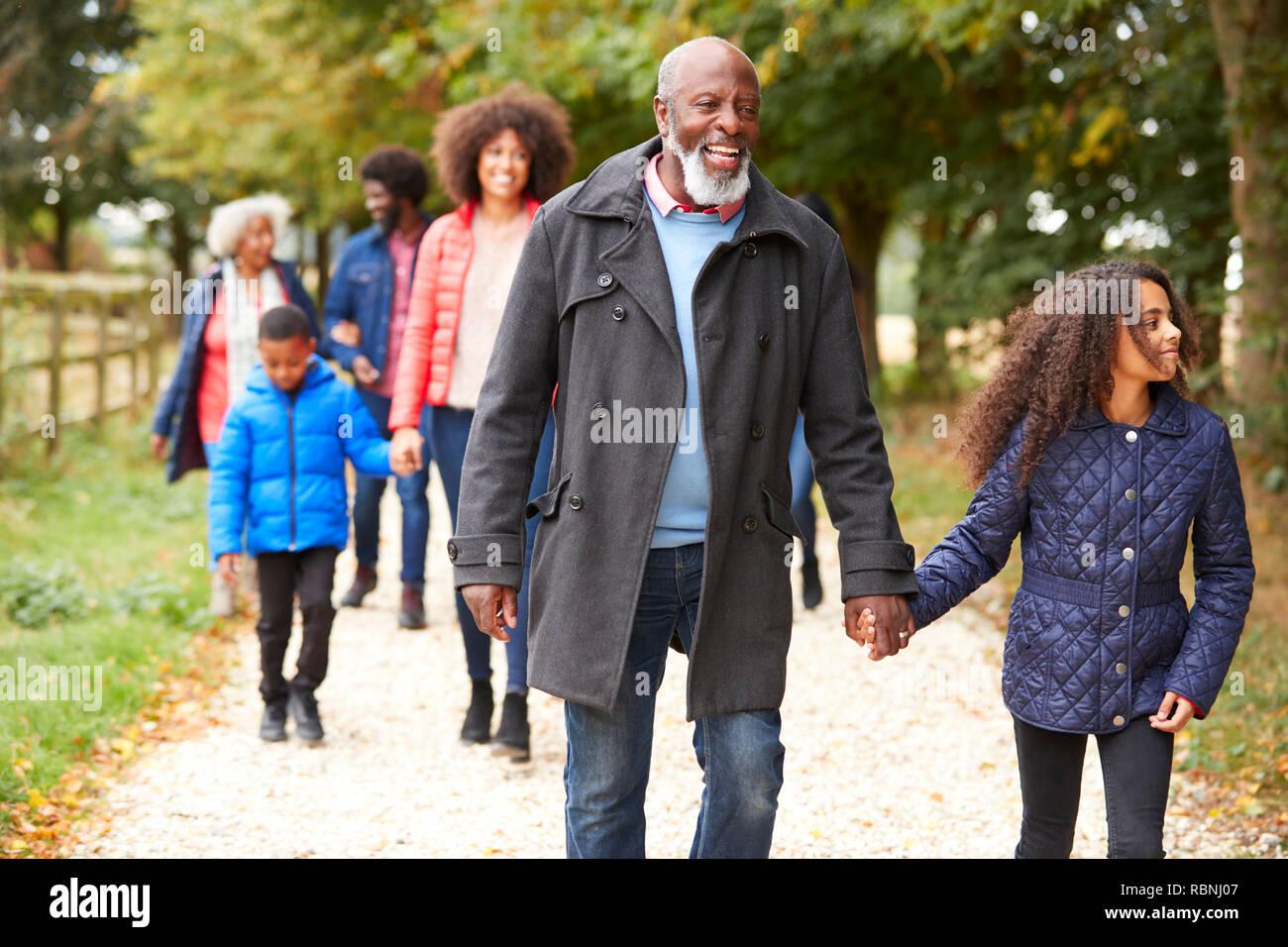 Familia de generación múltiple en otoño de caminar juntos en el campo Foto de stock
