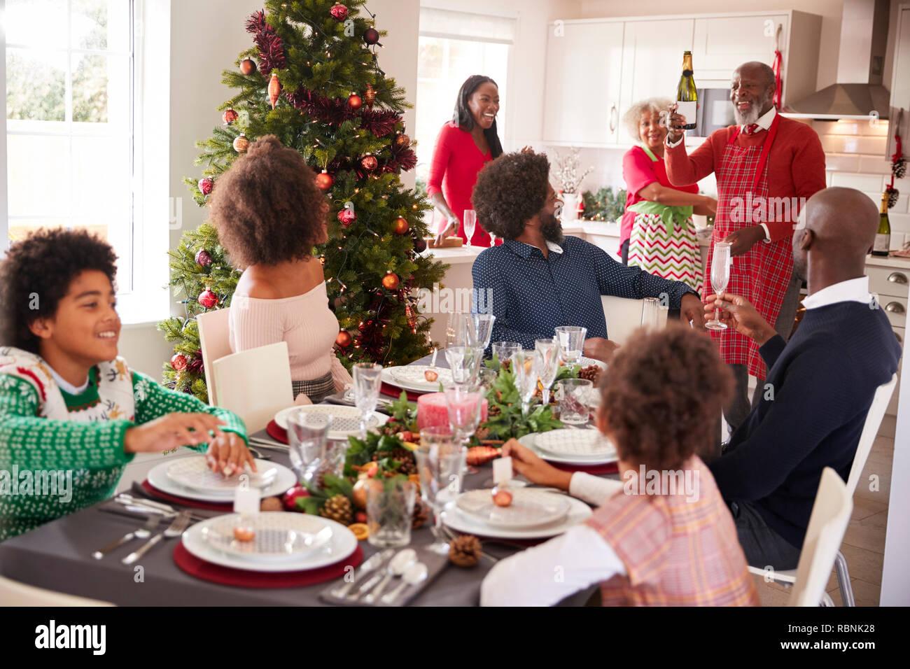 Raza mixta, multi generación reunión familiar en el comedor a sentarse para la cena de Navidad, el abuelo la celebración de botella de champán Imagen De Stock
