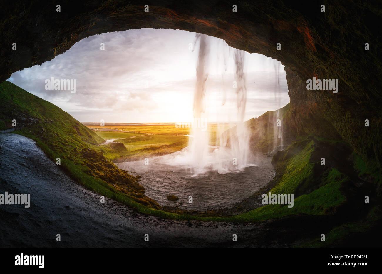 Una vista perfecta de la famosa cascada Seljalandsfoss potente en la luz del sol. Hermosa y dramática escena. Atracción turística popular. Islandia, lugar de ubicación Foto de stock