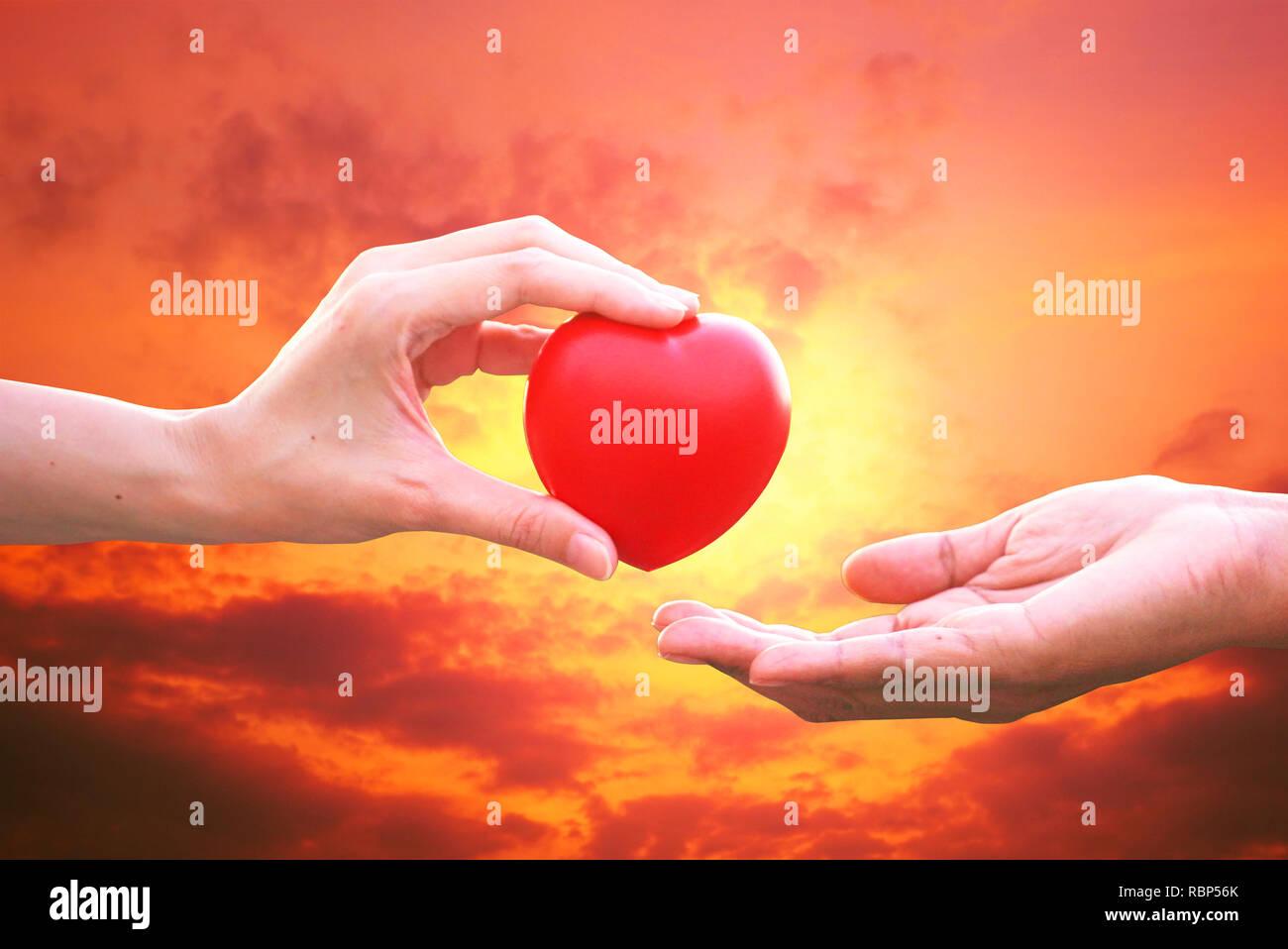 Amigo 's mano dar corazón rojo para alentar perdedor con el atardecer de fondo del cielo Imagen De Stock