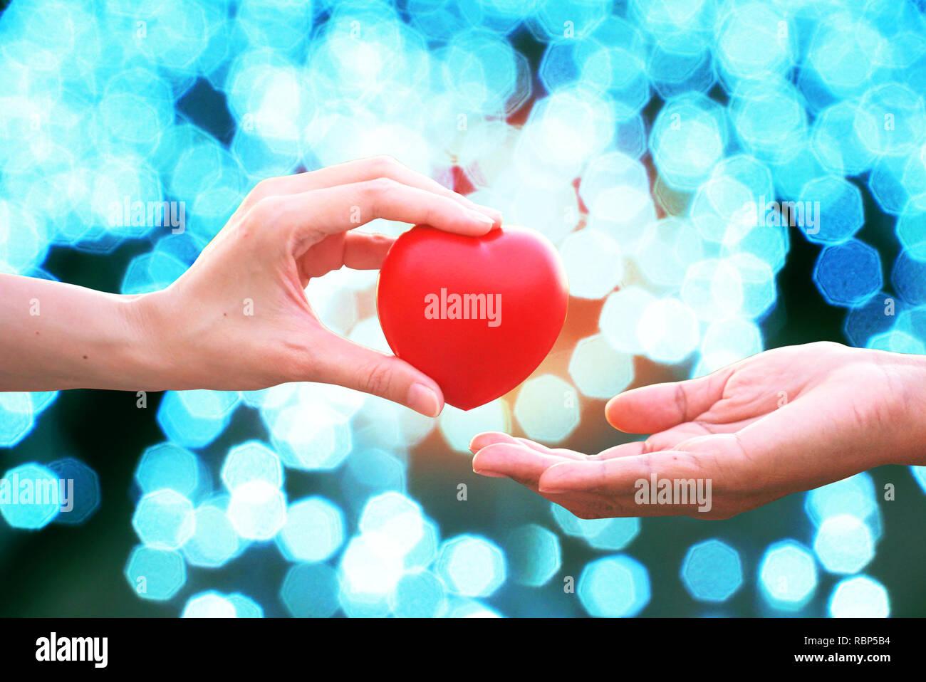 Amigo 's mano dar corazón rojo para alentar perdedor con sunset bokeh de fondo abstracto Imagen De Stock