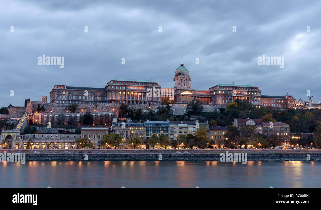 Castillo de Buda, con vistas al río Danubio, en Budapest. Es temprano en la noche, y el castillo está iluminado con luces, reflexionando sobre el río Foto de stock