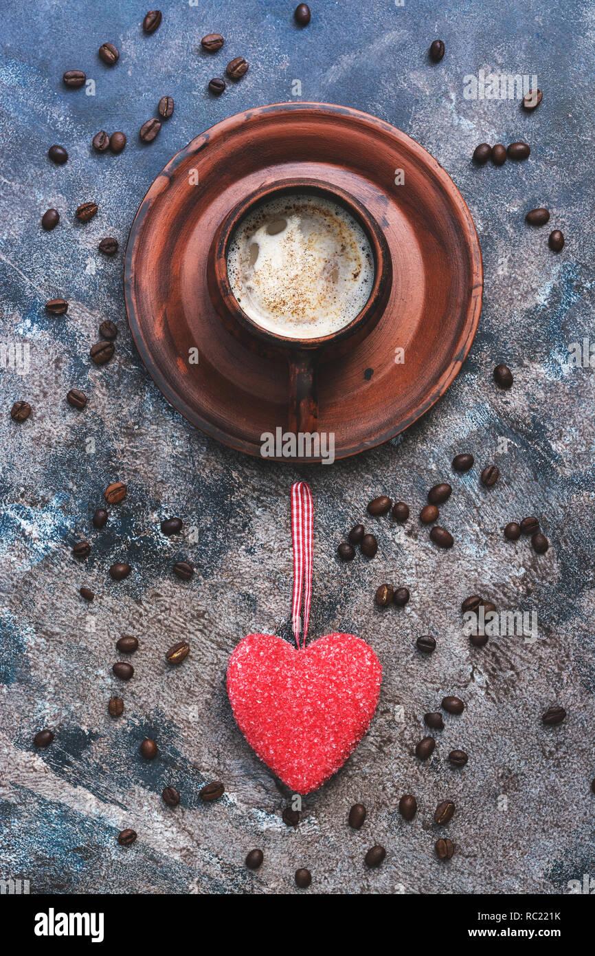 Café caliente y el corazón rojo sobre un fondo abstracto rústico. El concepto de celebración, el día de los enamorados. Vista desde arriba Foto de stock
