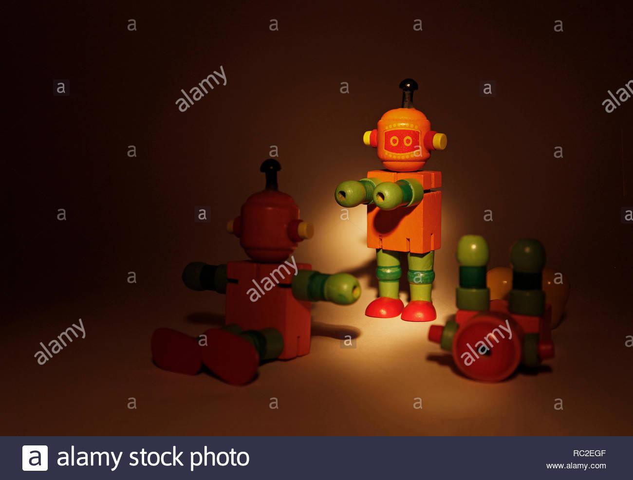 Studio escena, con toques de agresión / confrontación / violencia, utilizando 3 robots de juguete de madera en un foco. Copie el espacio con fondo oscuro. Imagen De Stock