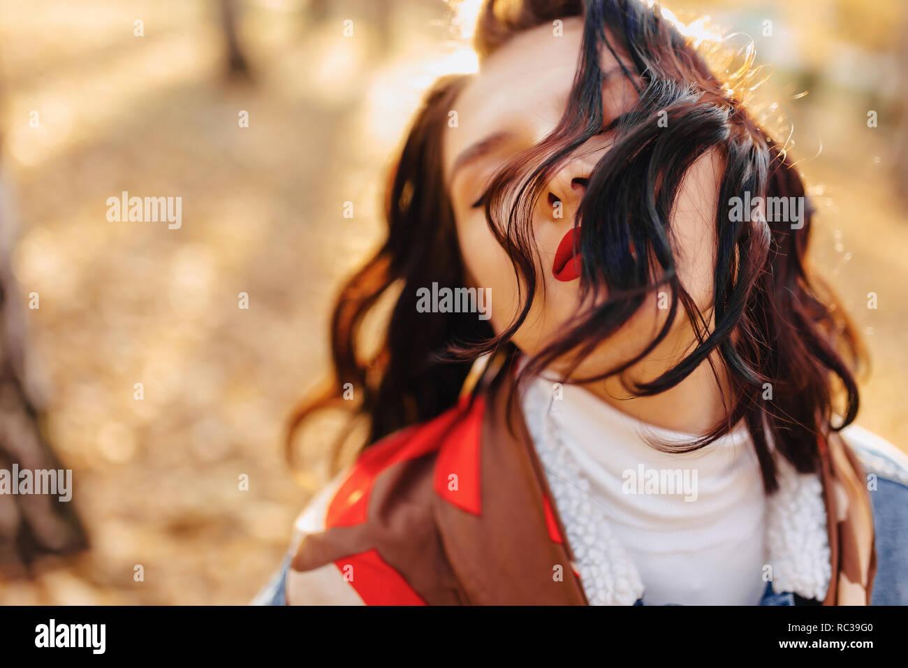 Joven chica bonita con labios rojos y pelo corto en un abrigo de mezclilla camina en la soleada ciudad de otoño Foto de stock