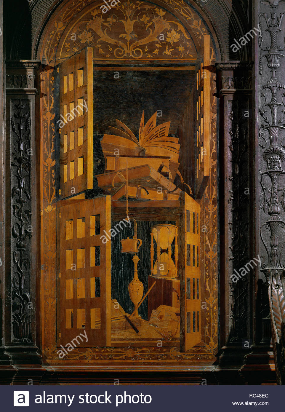 Los libros y el reloj en un armario. Incrustaciones de madera de la sillería del coro (1499). Autor: Fra Giovanni da Verona. Lugar: Iglesia de Santa Maria in Organo, Verona, Italia. Imagen De Stock