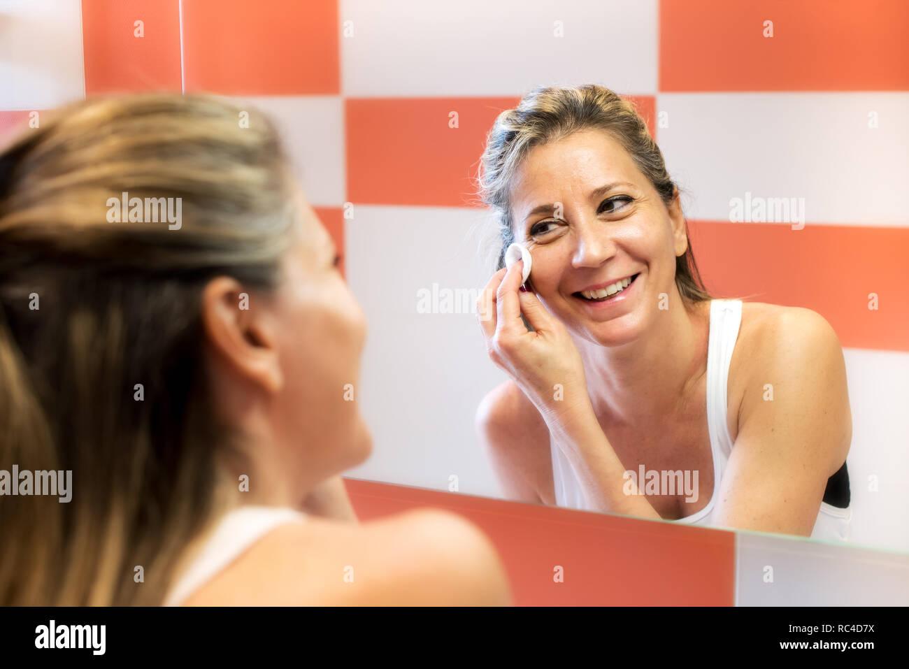 Sonriente mujer rubia madura en camiseta blanca quitando el maquillaje con algodón, mirando su reflejo en el espejo y riéndose. Busto retrato de re Imagen De Stock