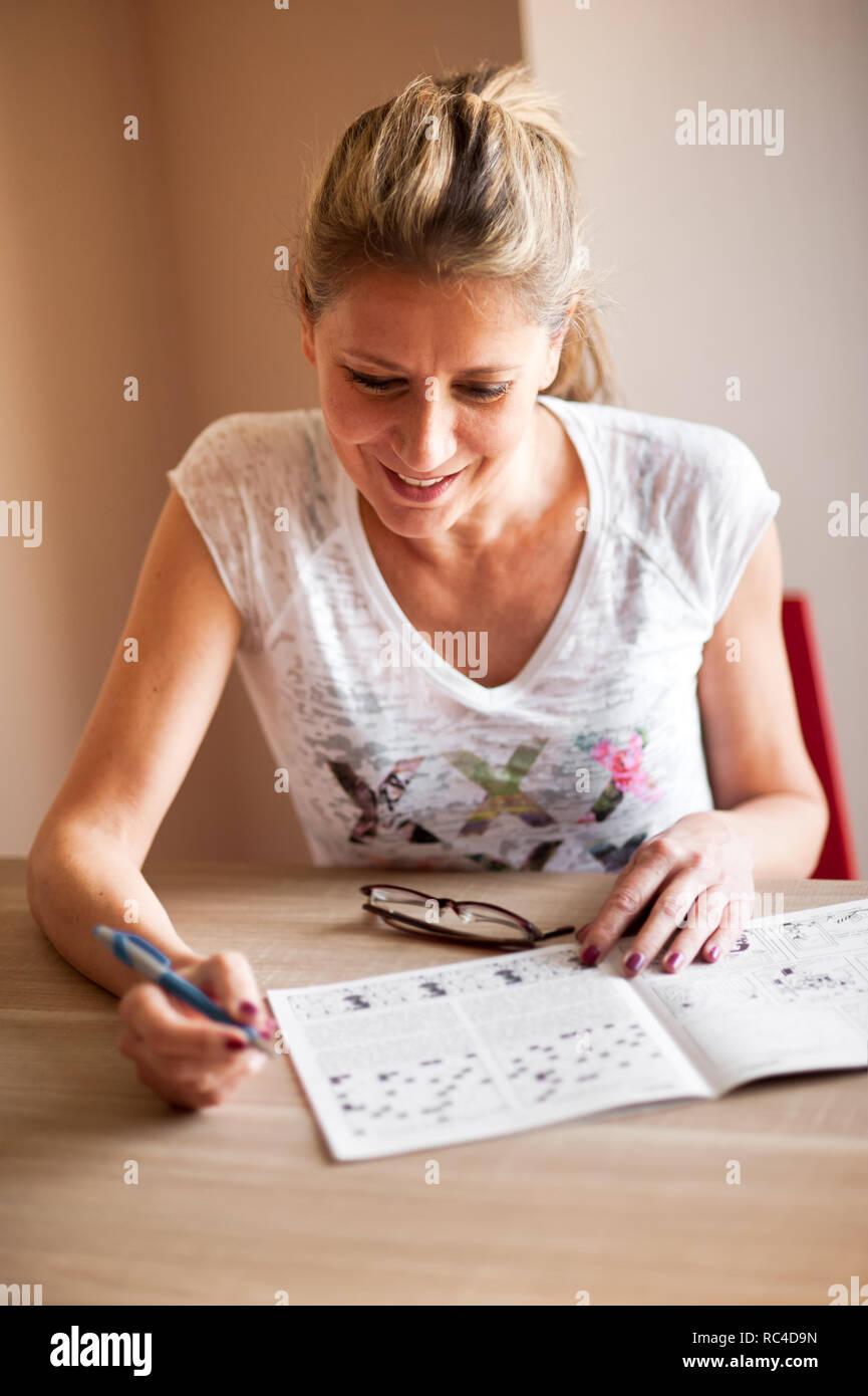 b3d6e130e3832 Mujer en camisa blanca sentado en la mesa de la habitación y resolver  crucigramas