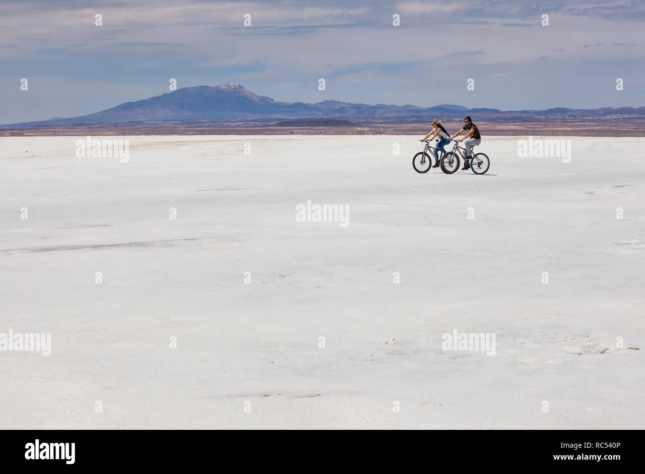 Una joven pareja se lanzó en la aventura de un ciclo de vida, puesto que a través de las vastas y abra el Salar de Uyuni, que disfrutan de libertad y hermosas vistas. Imagen De Stock