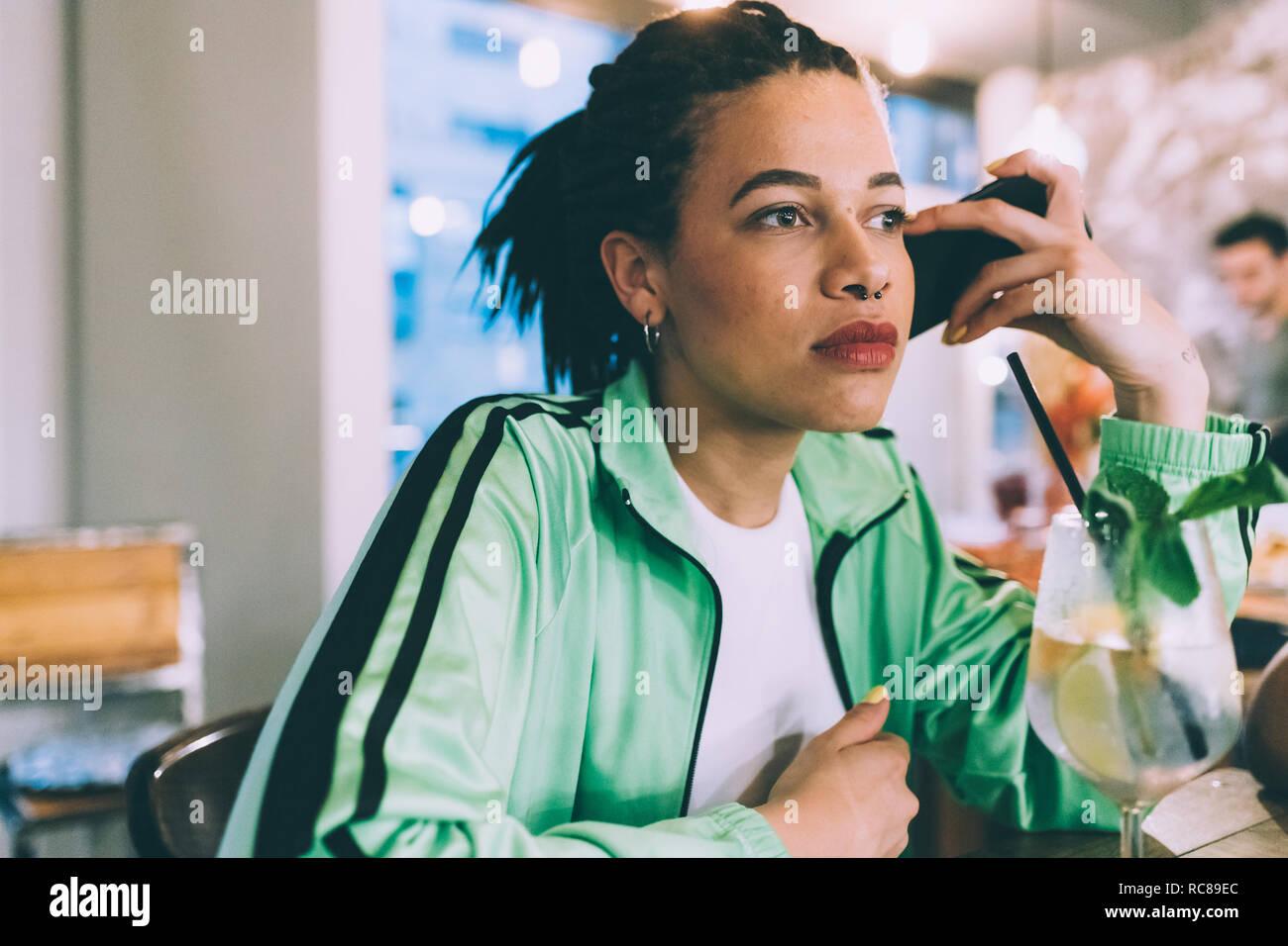 Mujer escuchando al mensaje en el móvil mientras beben en bares Foto de stock