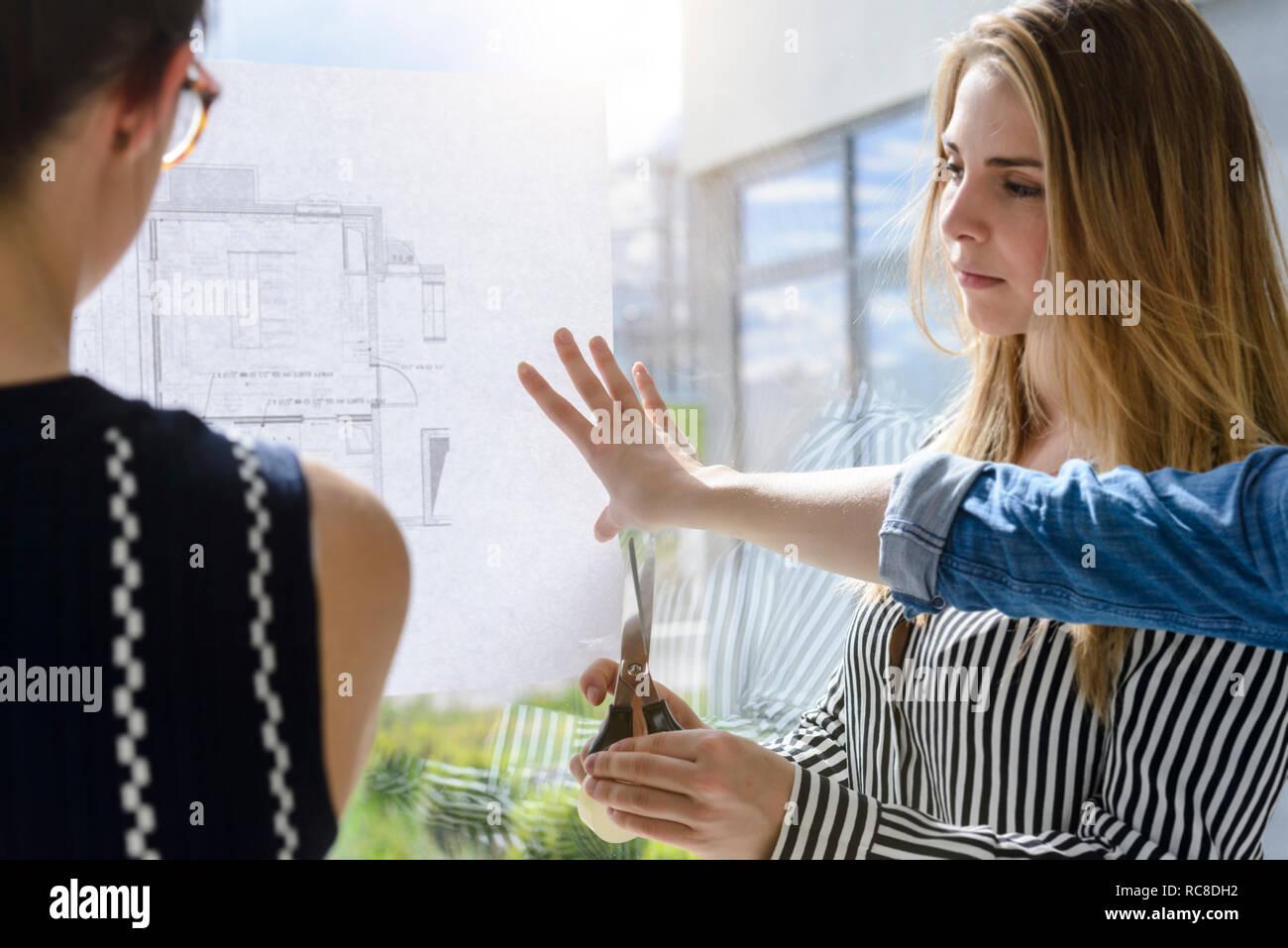 Compañeros discutiendo planes sobre la pared de vidrio Foto de stock