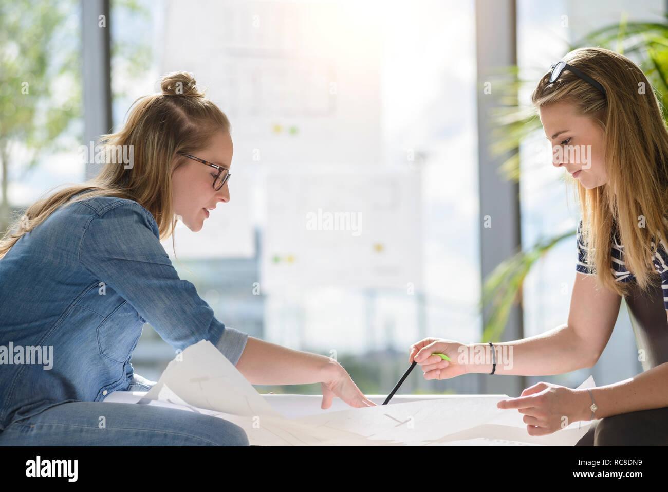 Los colegas de ideas a través de gráficos en la brillante luz del sol Foto de stock