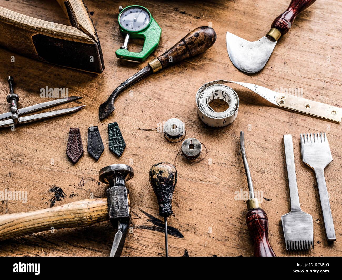 Leatherworker's Workbench con martillo, cinta métrica y herramientas especializadas, todavía la vida Foto de stock