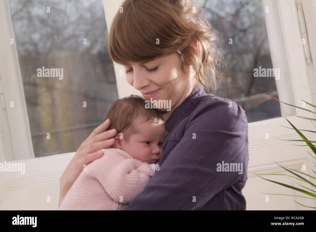 Junge Mutter ihre Tochter hält neugeborene im, brazo tipo das ist 12 Tage alt   joven madre sostiene a su bebé recién nacido en sus brazos - el bebé ist 12 días Foto de stock