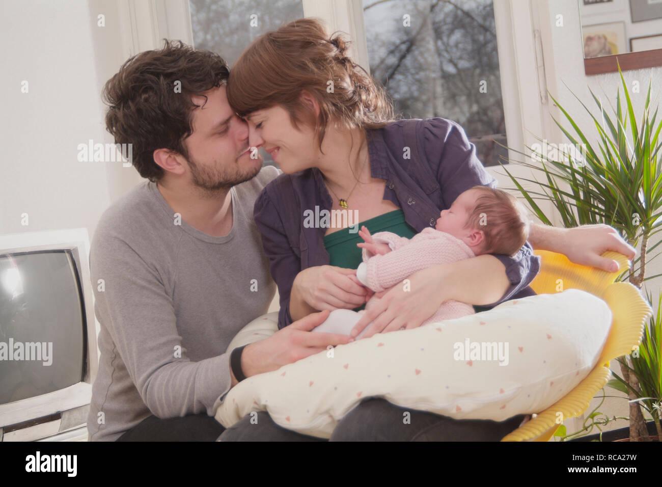 Junge Eltern halten ihre Tochter neugeborene im, brazo tipo das ist 12 Tage alt | padres jóvenes sostiene a su bebé recién nacido en sus brazos - el bebé ist 12 Foto de stock