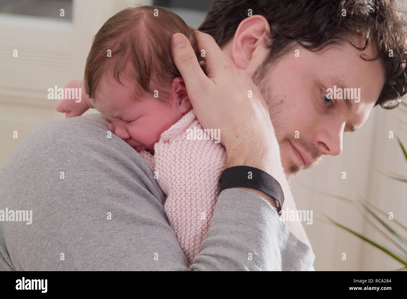 Junger hält seine Tochter neugeborene im, brazo tipo das ist 12 Tage alt | padre joven sosteniendo a su bebé recién nacido en sus brazos - el bebé ist 12 días de antigüedad. Foto de stock