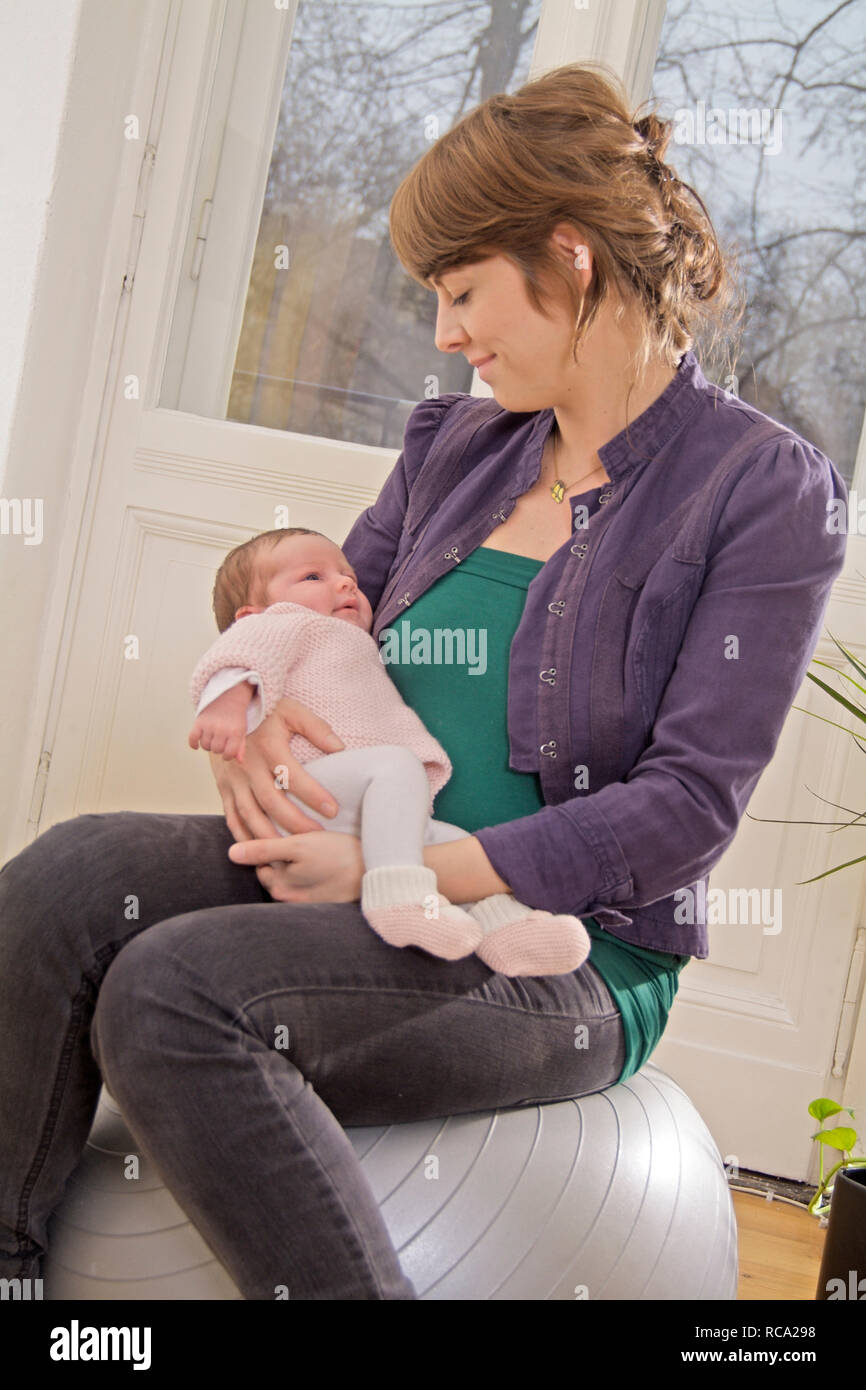 Junge Mutter ihre Tochter hält neugeborene im, brazo tipo das ist 12 Tage alt | joven madre sostiene a su bebé recién nacido en sus brazos - el bebé ist 12 días Foto de stock