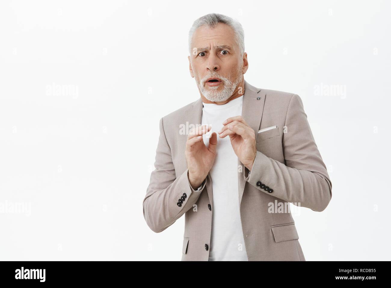 Retrato de intensa disgustado macho viejo hombre en traje elegante celebración manos presionado a pecho paso atrás de desagrado y aversión sensación escalofriante y tímido posando con fondo blanco. Imagen De Stock