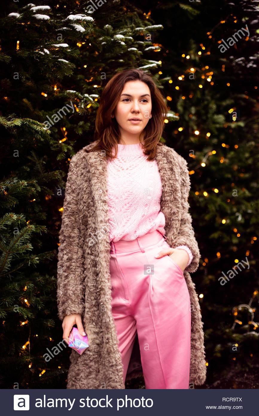 952c3549a Mujer joven en eco piel y ropa rosa caminando en la calle decorado de  Navidad Imagen
