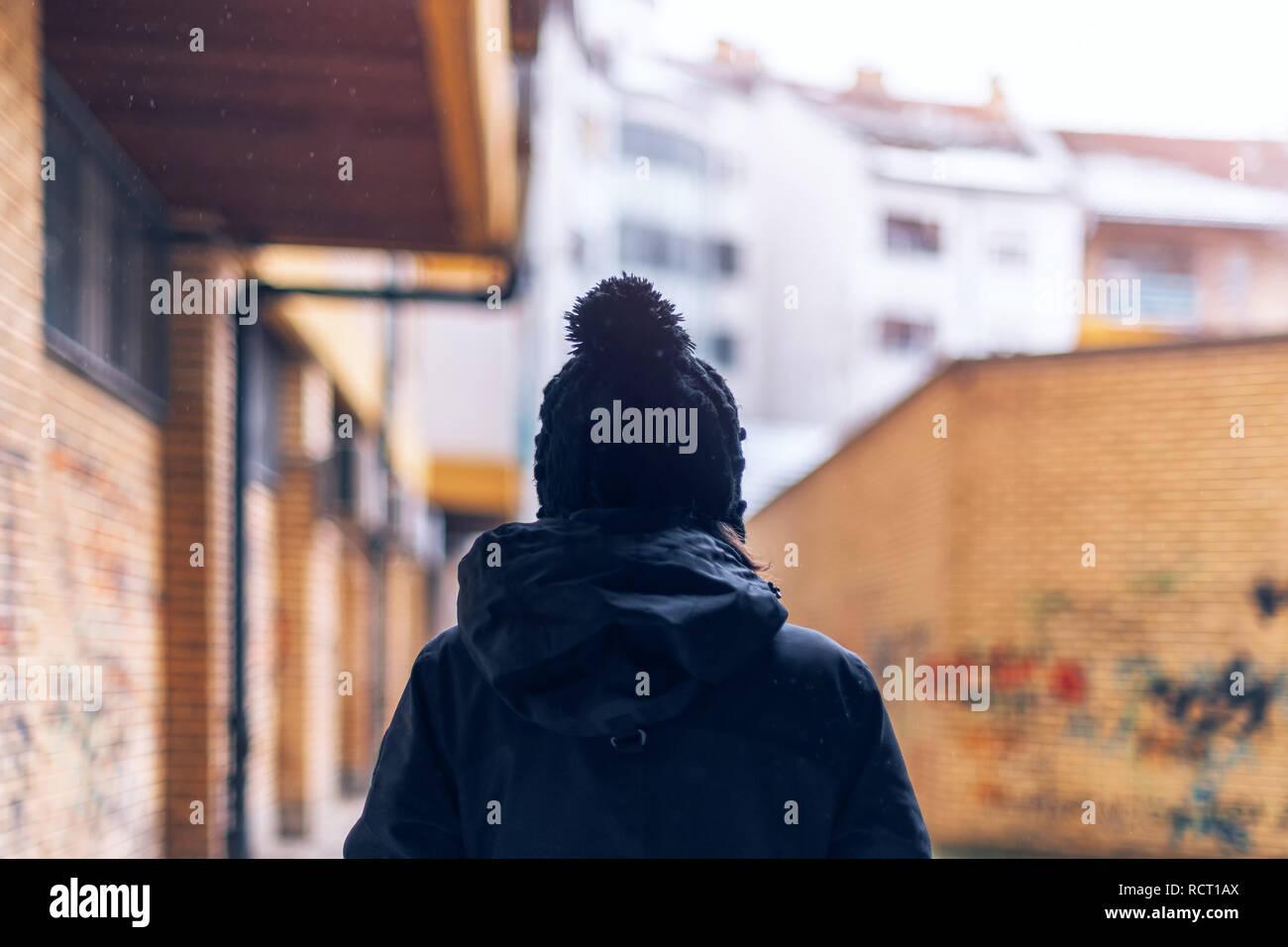 Vista trasera de una mujer adulta casual caminando por las calles de la ciudad urbana durante la luz nevadas en invierno Foto de stock