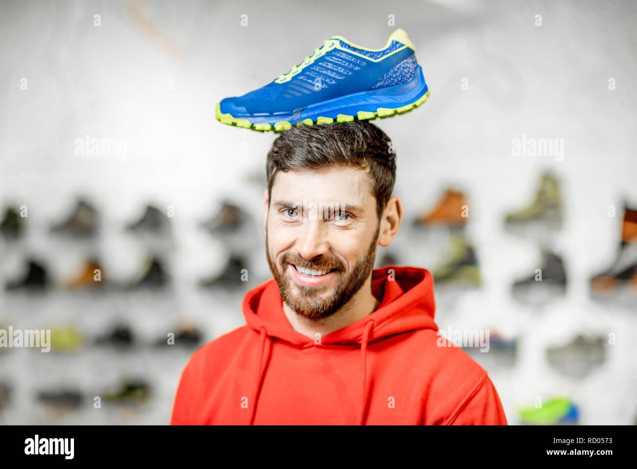 Gracioso retrato de un hombre con calzado deportivo en su cabeza de pie en la tienda de deportes Imagen De Stock