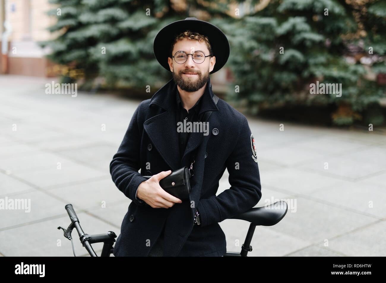Joven apuesto hombre de gafas y sombrero de pie con su bicicleta en la calle Foto de stock
