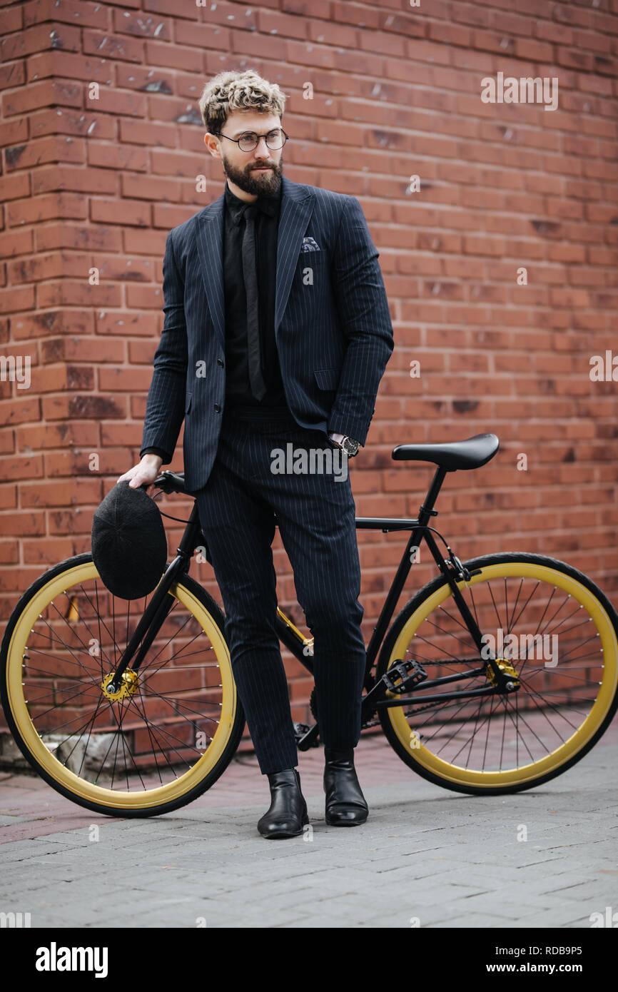 Empresario elegante de pie con su bicicleta contra la pared de ladrillo Foto de stock