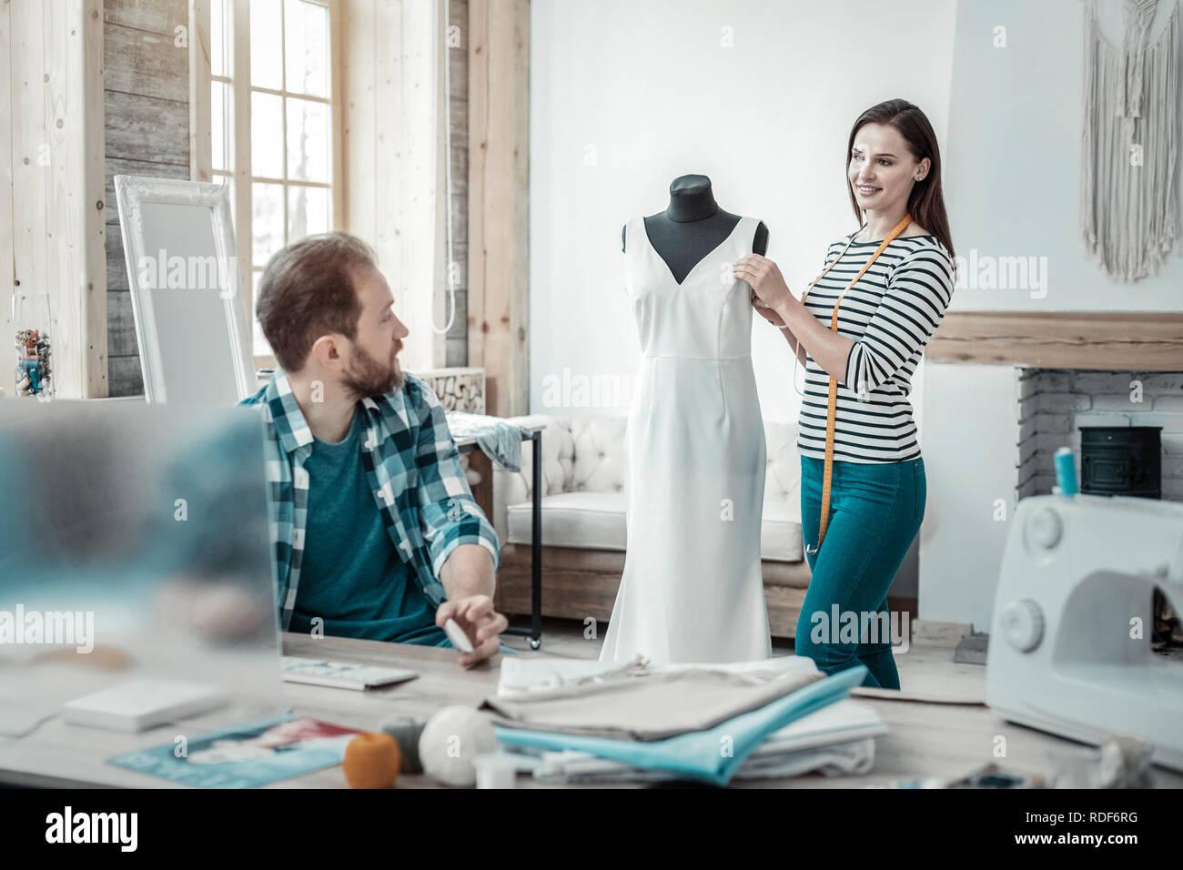 47fc0dc036 Morena de pie cerca del diseñador con forma de vestido largo vestido blanco  Imagen De Stock