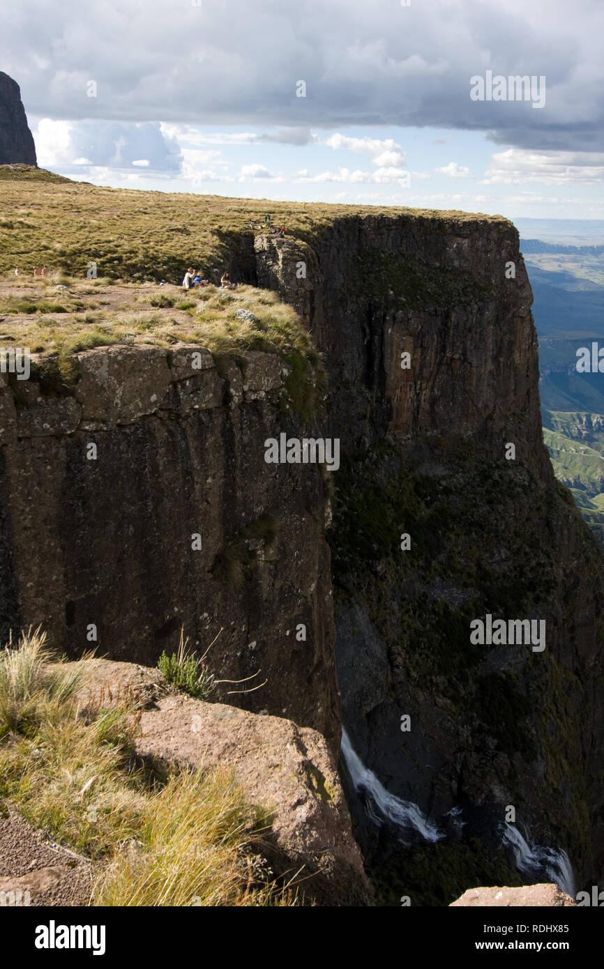 Los excursionistas se sientan encima de Tugela Falls en el Anfiteatro formación en las montañas Drakensberg, el Parque Nacional Royal Natal, KwaZulu-Natal, Sudáfrica. Foto de stock