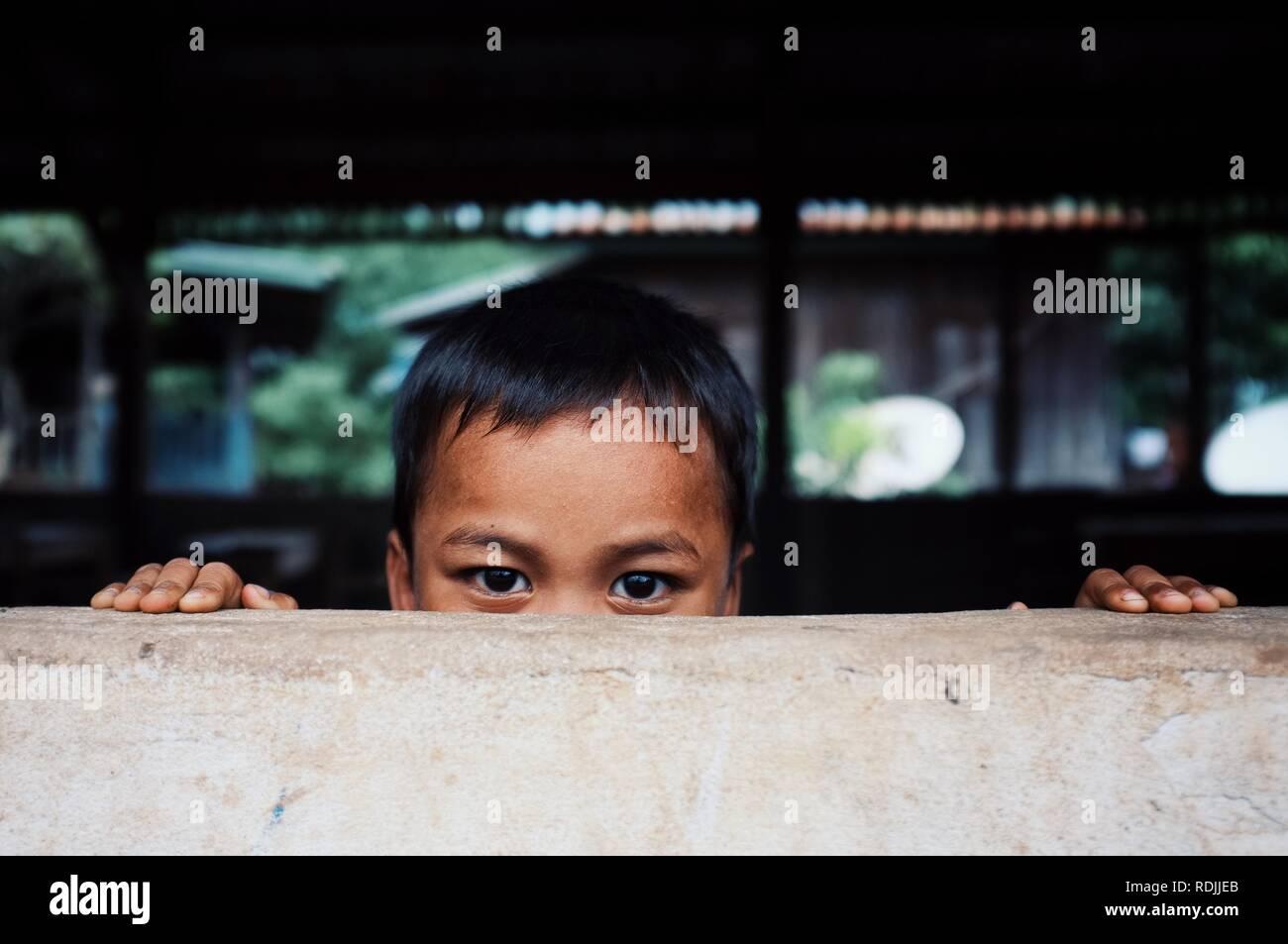 Luang Namta / Laos - Jul 06 2011: lindo chico escondido detrás de un muro pico justo encima de su cabeza Foto de stock
