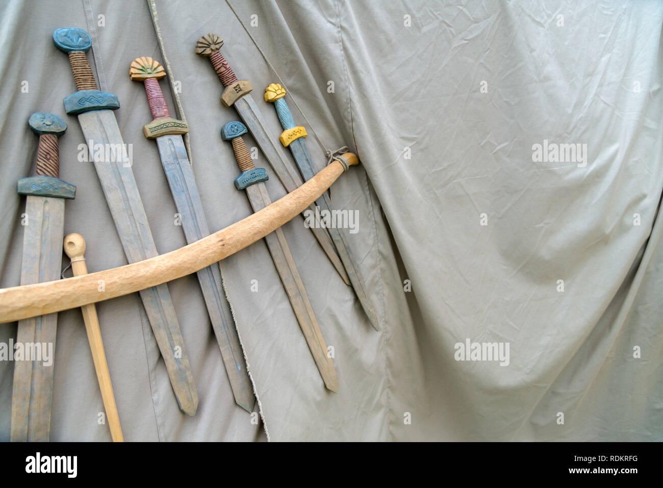 Espadas artesanales de madera colgando de la cuerda en tejido gris de fondo. Armas medievales para combate aparece en tejido gris textura Imagen De Stock