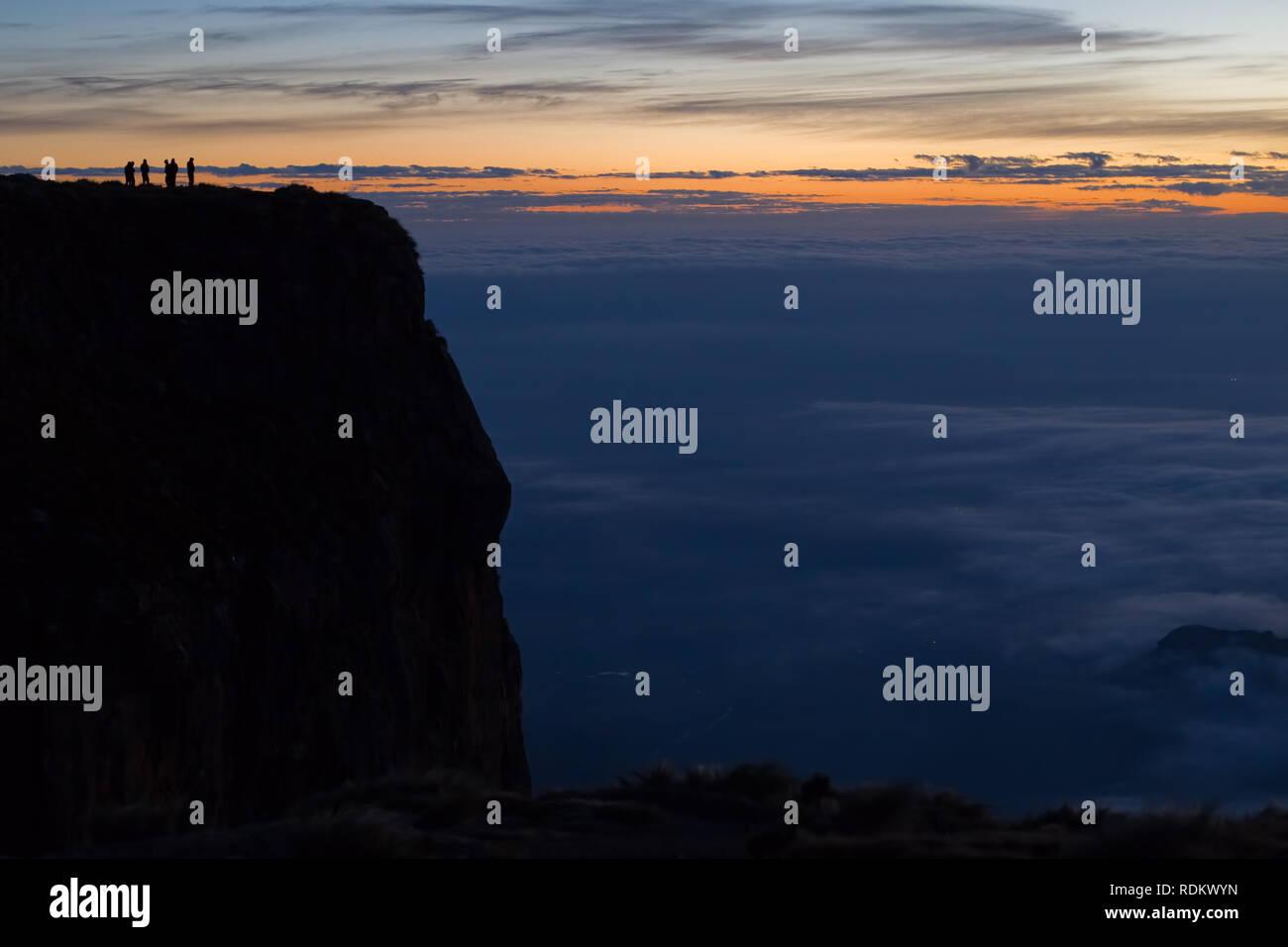 Los excursionistas se reúnen para la puesta de sol sobre el borde del anfiteatro en el Parque Nacional Royal Natal. Debajo de ellos, la montaña da paso a una caída de 1000 m. Foto de stock