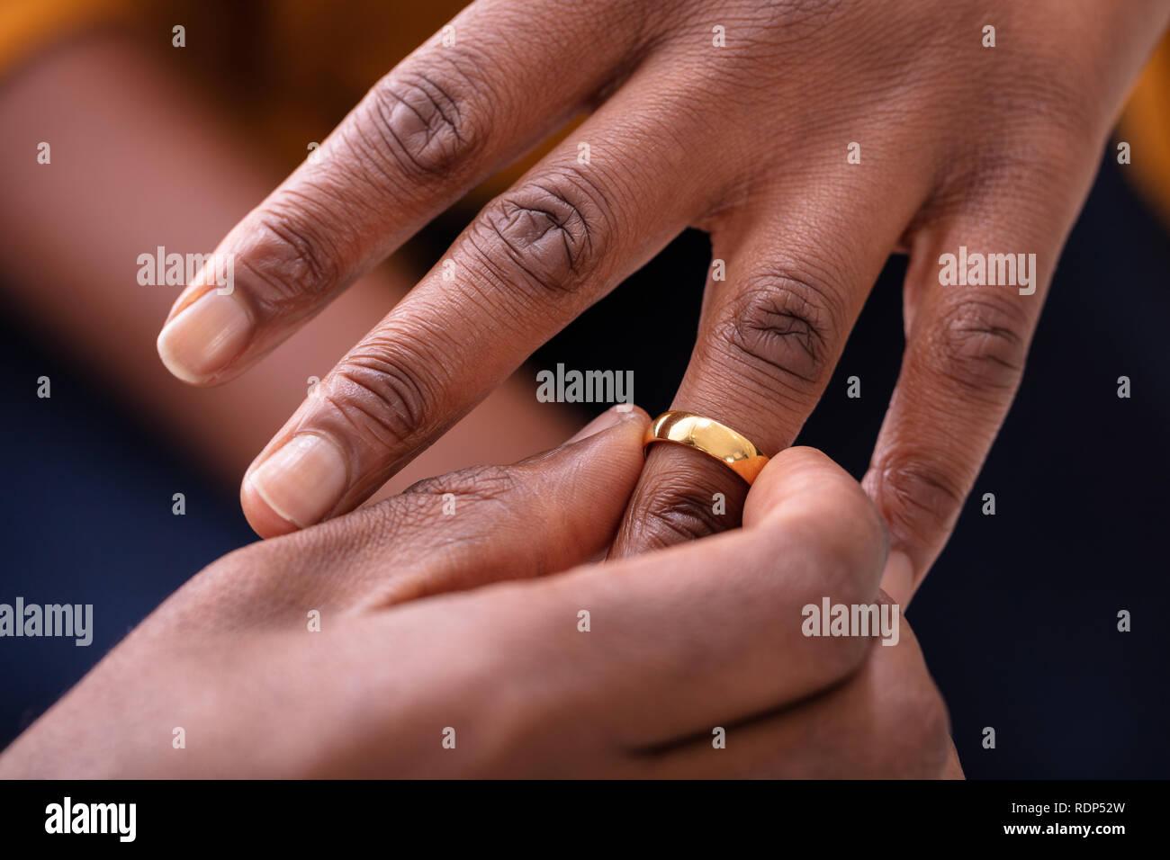 d9cbf81f6bbb Close-up de la mano del hombre poniendo Golden Anillo de compromiso en el  dedo