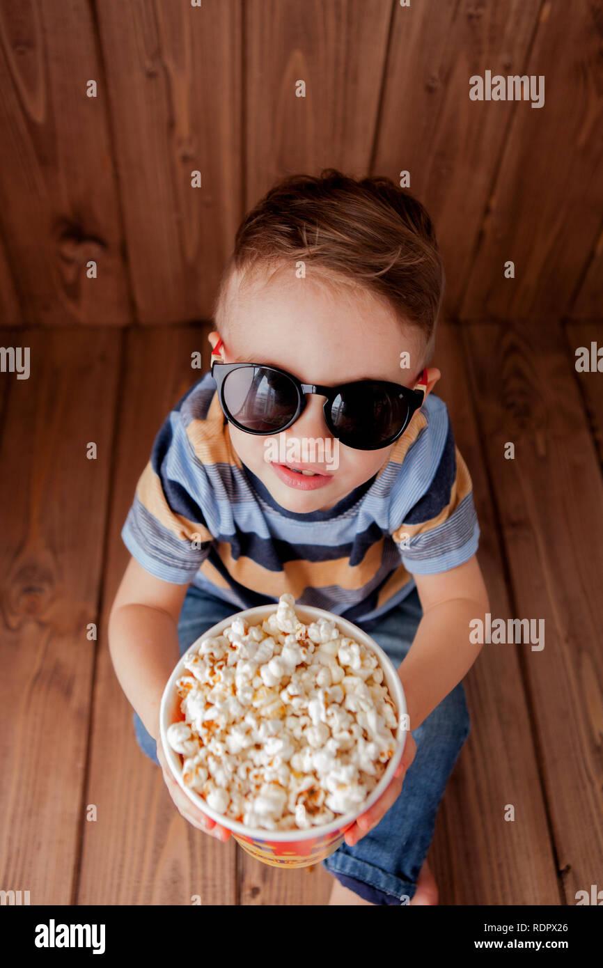 a990550a8e Poco chico lindo bebé niño 2-3 años , cine 3D gafas sosteniendo la cuchara  para palomitas, comer comida rápida sobre fondo de madera.