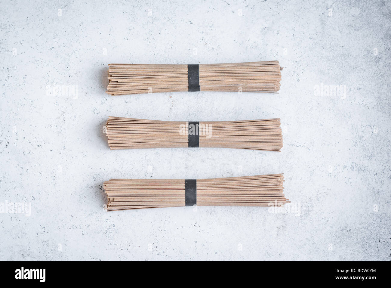 Fideos Soba - ingrediente alimentario tradicional asiática. Paquete de alforfón fideos soba en hormigón blanco de fondo, vista superior, espacio de copia. Foto de stock