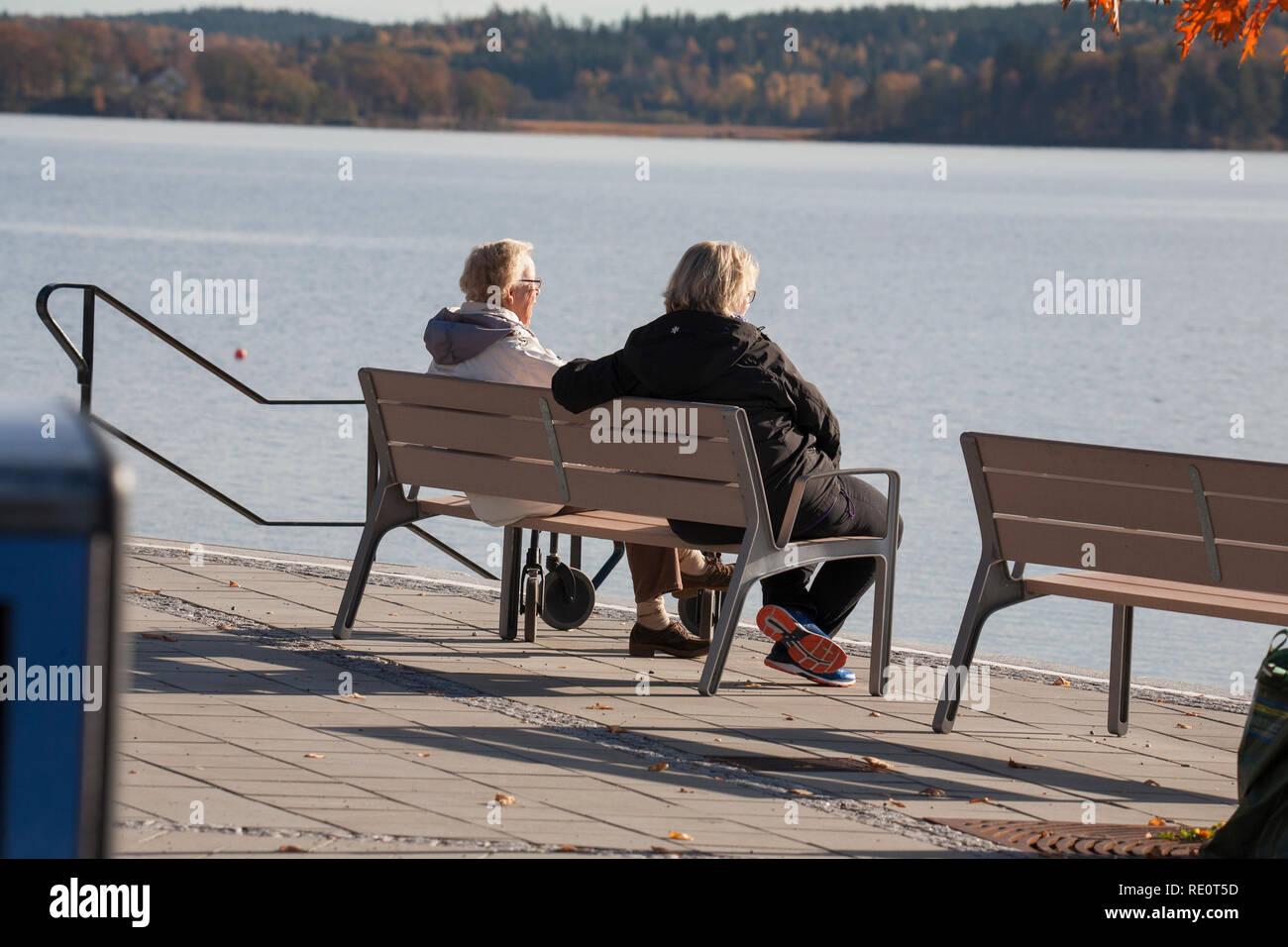 Señoras en un banco por el agua hablando en el otoño de sun Imagen De Stock
