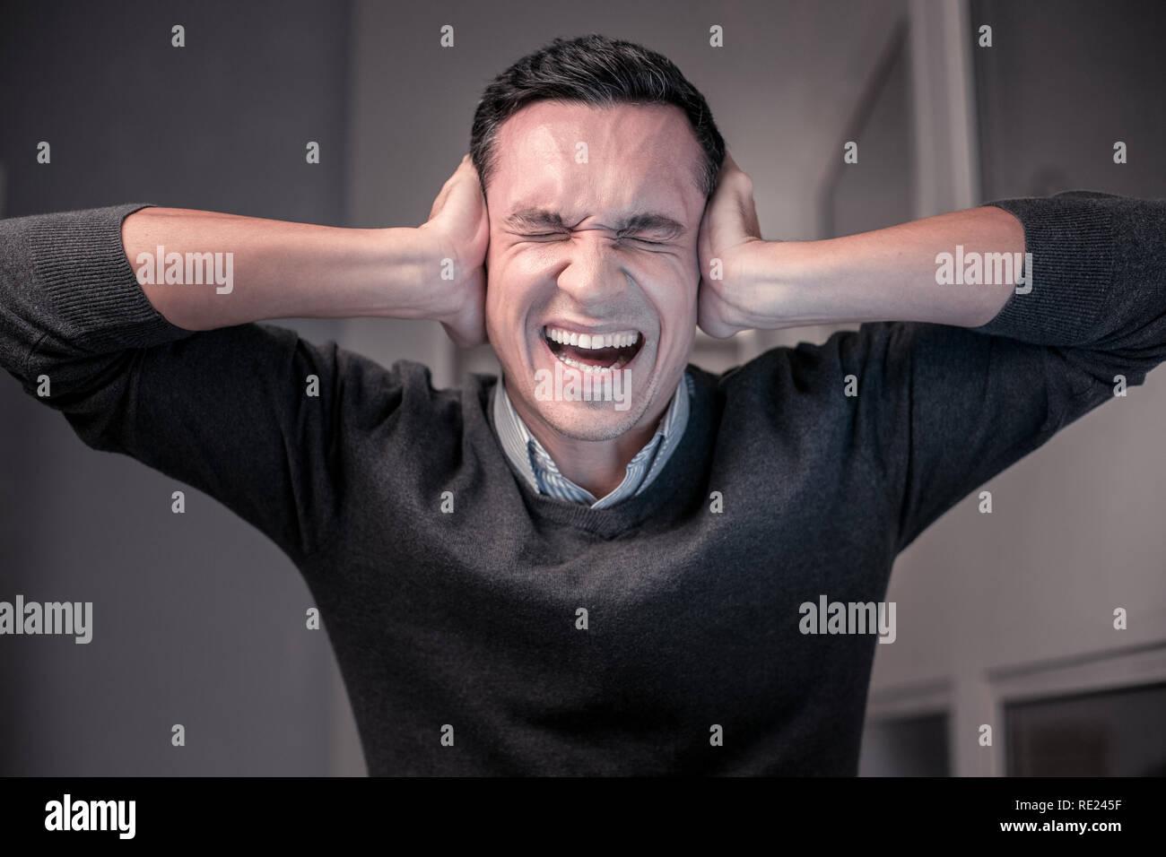 Enojado infeliz hombre teniendo un trabajo muy estresante Imagen De Stock