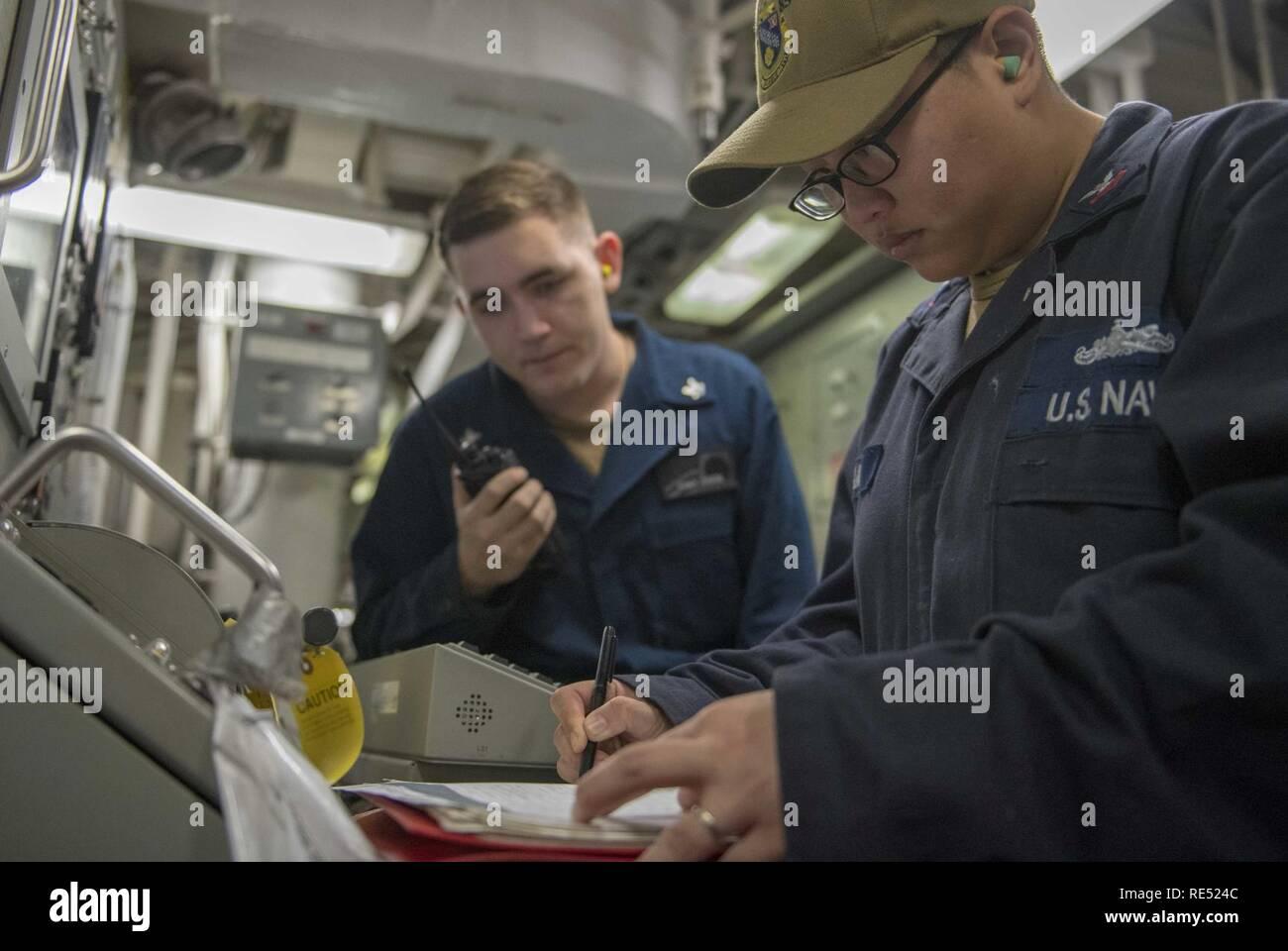 El Mar de China oriental (Ene. 1, 2018), Técnico de sistemas de Turbina de Gas (Eléctrico) 1ª clase Vidamo Cleo, en Lisle, Illinois, Derecho y Técnico de sistemas de Turbina de Gas (mecánica) de 3ª clase Cristóbal Garza, de Arlington, Texas, compruebe una turbina de gas a los parámetros del sistema a bordo de la clase Arleigh Burke de misiles guiados destructor USS McCampbell (DDG 85). Es McCampbell desplegadas a la séptima Flota de EE.UU. zona de operaciones en apoyo de la seguridad y la estabilidad en la región del Indo-Pacífico. Foto de stock