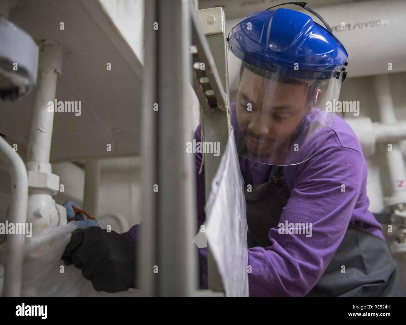El Mar de China oriental (Ene. 1, 2018), técnico del sistema de turbina de gas (mecánica) Bombero Malik Hughes, de Louisville, Ky., drena un cabezal hidráulico tanque a bordo de la clase Arleigh Burke de misiles guiados destructor USS McCampbell (DDG 85). Es McCampbell desplegadas a la séptima Flota de EE.UU. zona de operaciones en apoyo de la seguridad y la estabilidad en la región del Indo-Pacífico. Foto de stock