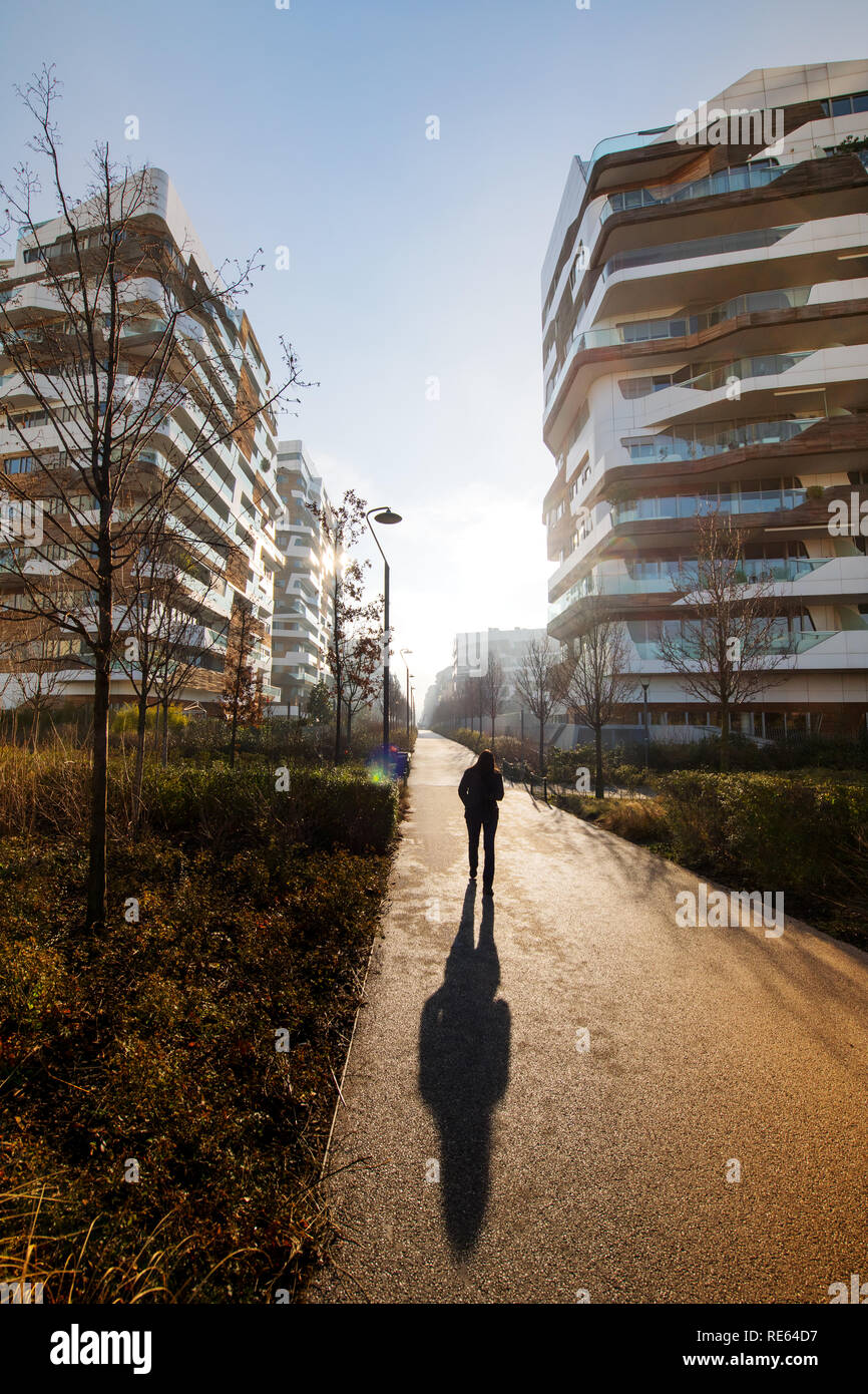 Hombre caminando en un elegante complejo de apartamentos en un amanecer o  atardecer proyectando una larga 228cf546d8c8