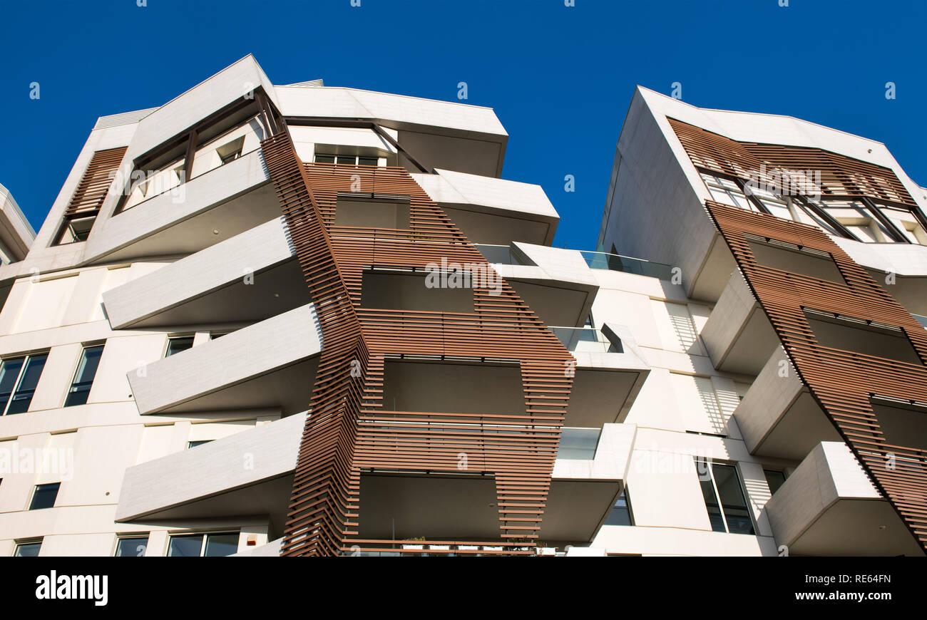 Moderno diseño angular altos bloques de apartamentos vista desde abajo, mostrando revestimiento externo contra un cielo azul Imagen De Stock