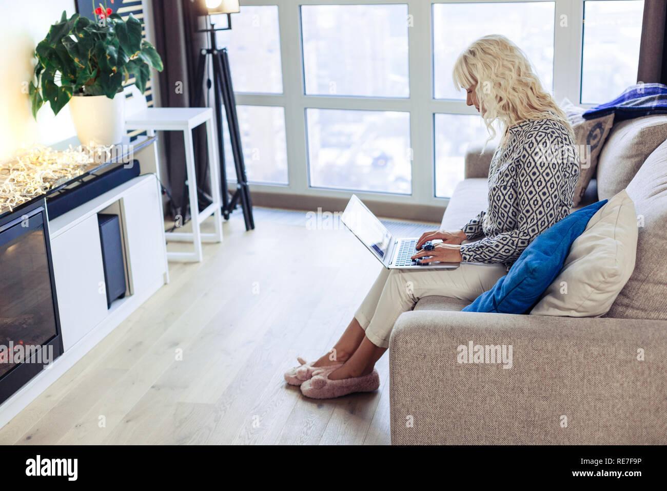 Bonita mujer atractiva sentado en el sofá en casa Foto de stock