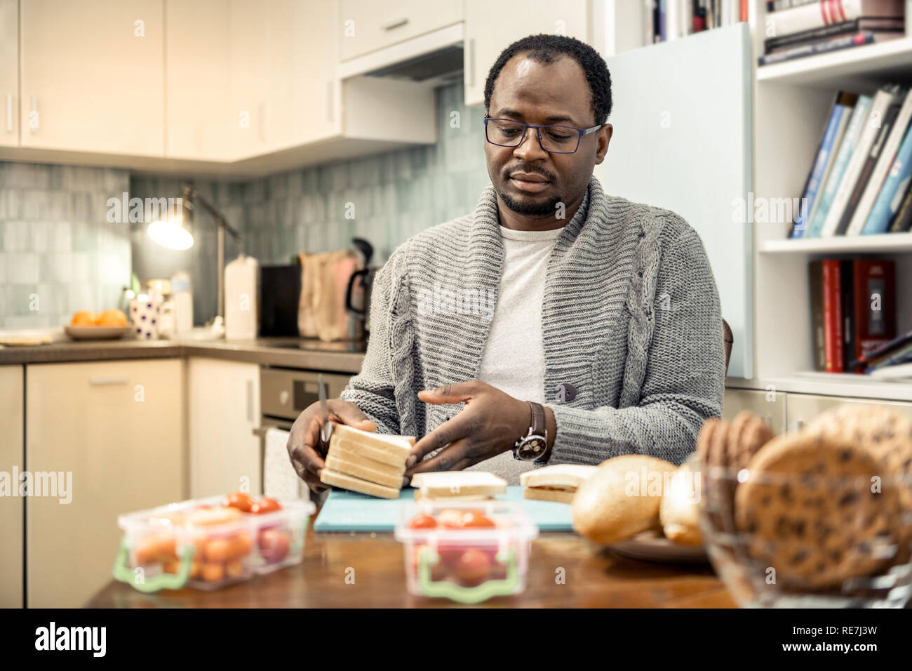 Padre bondadoso gafas cocinar sandwiches para viaje familiar Foto de stock